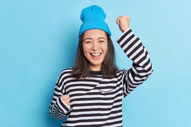 Isolated shot of cheerful happy asian girl raises hands dances carefree celebrates success smiles broadly expresses sincere emotions and happines