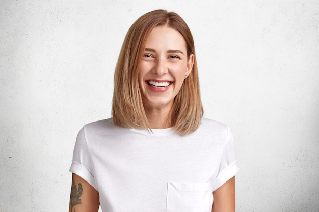 Isolated shot of cheerful satisfied young female with pleasant look, broad chaming smile, tattooed arm, dressed in casual whte t shirt, poses in studio, glad to achieve success at work and life