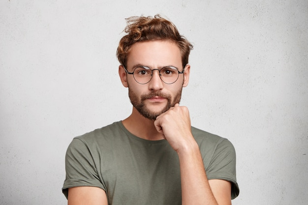 Isolated shot of confident bearded man looks directly into camera, has serious expression
