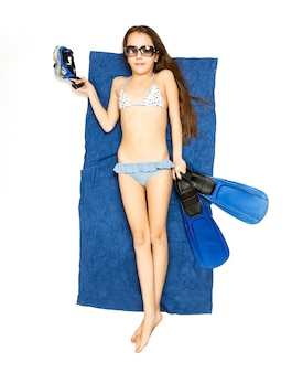 Isolated shot of cute girl lying on blue towel with flippers and snorkeling mask