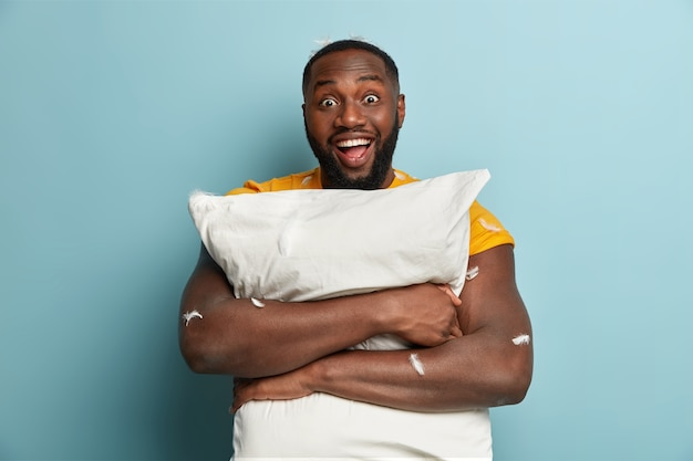 Isolated shot of dark skinned young man with optimistic gaze carries pillow, has fun in bedroom, enjoys comfort and peaceful domestic atmosphere at home, expresses good emotions. bed time concept