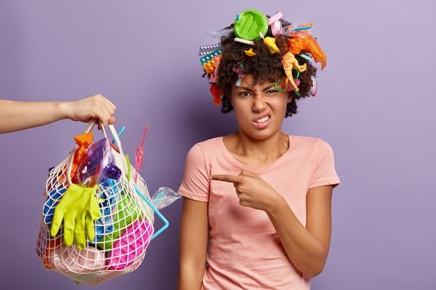 Colpo isolato di disperata donna dalla pelle scura punta al sacco della spazzatura che trasporta una persona sconosciuta, impegnata nella giornata mondiale dell'ambiente, vestita con una maglietta casual, si trova sopra il muro viola, raccoglie la spazzatura