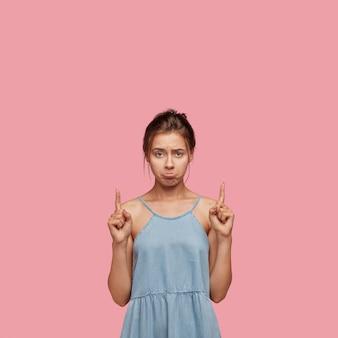 Colpo isolato di donna scontenta con espressione cupa, ha un aspetto cupo