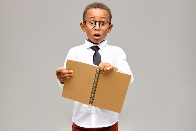Isolated shot of emotional shocked african pupil wearing white shirt, black tie and eyeglasses having surprised astonished look, keeping mouth widely, holding open blank copybook in his hands