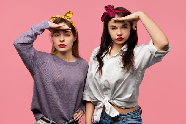 Colpo isolato di giovani donne sveglie allegre alla moda che indossano sciarpe sulla testa che tengono i palmi sulla fronte e scrutano nell'orizzonte di scansione a distanza durante la ricerca di qualcosa. linguaggio del corpo