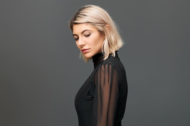 Isolated shot of fashionable trendy hipster with nose ring and blonde bob hairdo wearing transparent black blouse posing at blank wall, having thoughtful facial expression, looking down