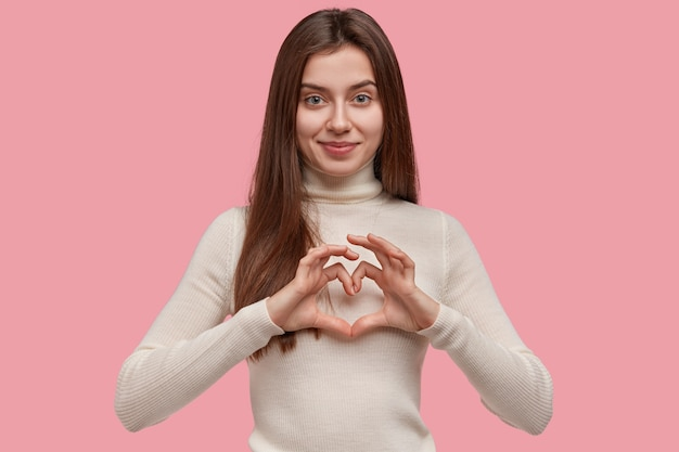 Isolated shot of friendly looking young girl shows heart gesture over chest, being in love with somebody, shows sympathy and care