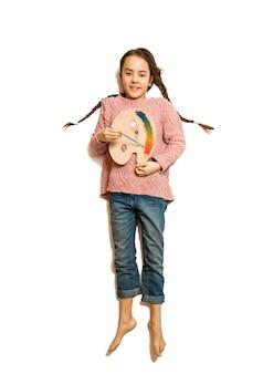 Изолированный снимок сверху улыбающейся девушки, держащей палитру и масляные краски