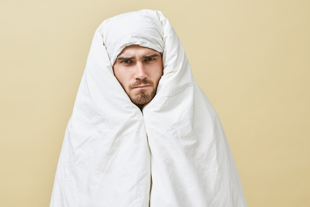 Isolated shot of frustrated sleepy young male having angry displeased facial expression frowning eyebrows, unwilling to got to work, preferring staying in warm bed instead, wrapped in white blanket