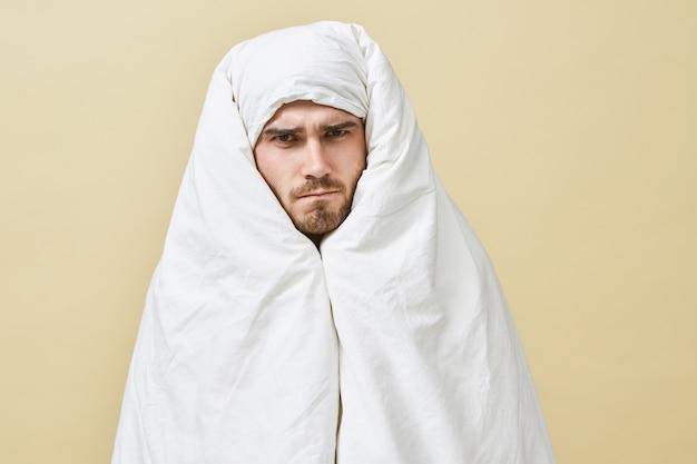 Colpo isolato di giovane maschio assonnato frustrato con espressione facciale arrabbiata e dispiaciuta sopracciglia accigliate, riluttante a mettersi al lavoro, preferendo invece stare nel letto caldo, avvolto in una coperta bianca