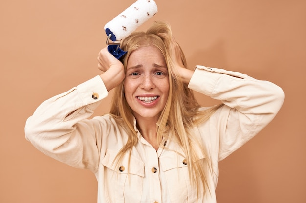 Colpo isolato di decoratore femminile giovane infelice frustrato con staffe che tengono le mani sulla sua testa avendo sottolineato l'espressione facciale perché non riesce a terminare la riparazione in tempo