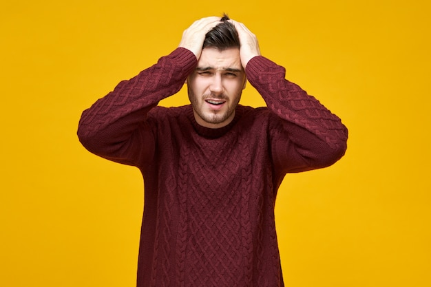 Isolated shot of frustrated young male in knitted pullover keeping hands on head and grimacing suffering from migraine because of stressful work, having painful facial expression, feeling unwell