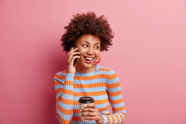 Isolated shot of good looking woman with afro hair looks happily away keeps smartphone near ear drinks takeaway coffee wears casual striped jumper isolated over pink wall
