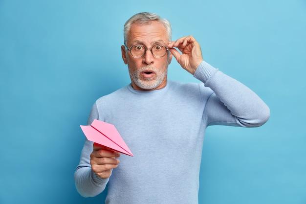 Colpo isolato di uomo dai capelli grigi trattiene il respiro tiene le mani sugli occhiali essendo spaventato tiene aeroplano di carta vestito con abiti casual isolato sopra la parete blu