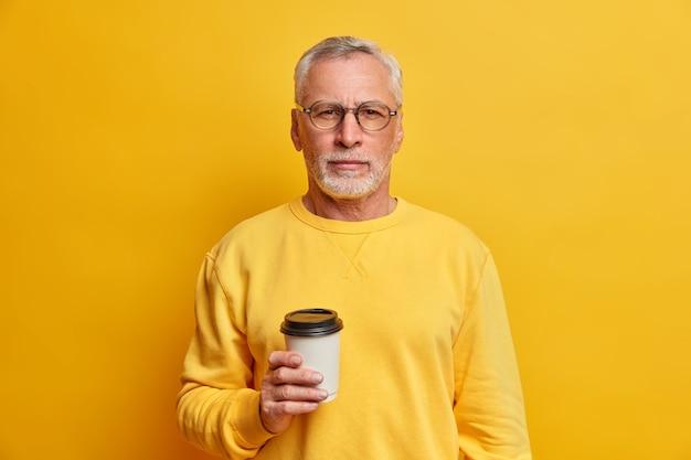 Colpo isolato di bell'uomo barbuto tiene caffè da asporto usa e getta e guarda seriamente davanti ha pausa vestito in pose luminose del ponticello contro il muro giallo