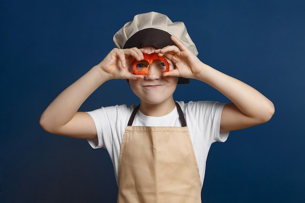 Isolated shot of handsome cute little boy in chef uniform holding slice of bell pepper at his face