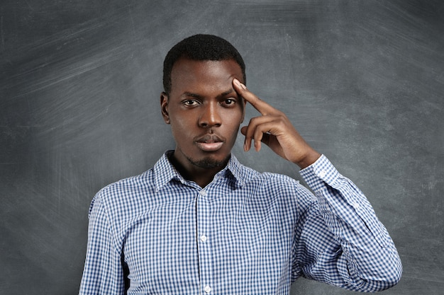 Isolated shot of handsome frustrated african man wearing shirt holding finger on his forehead as if trying hard to recollect something or solve serious problem, having concentrated look.