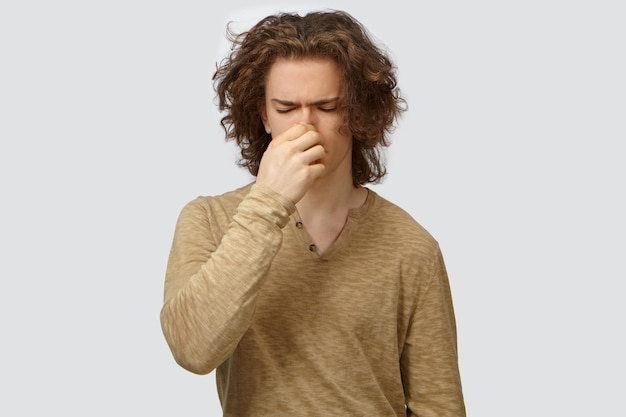 Isolated shot of handsome frustrated young european male in long sleeved top closing eyes and pinching nose, feeling disgusted because of bad smell or stink of sweaty armpits or dirty socks
