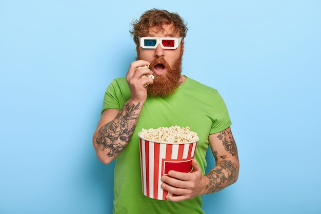 Isolated shot of handsome man has tattoo, ginger hair, watches movie, involved with story
