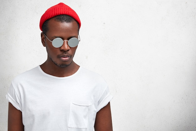 Isolated shot of handsome stylish black man in fashionable shades and hat, looks thoughtfully down, poses against white concrete