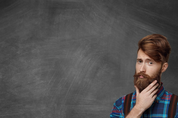 Isolated shot of handsome young man with stylish haircut dressed in checkered shirt and suspenders generating fresh ideas, touching his thick beard with thoughtful look, trying to remember something
