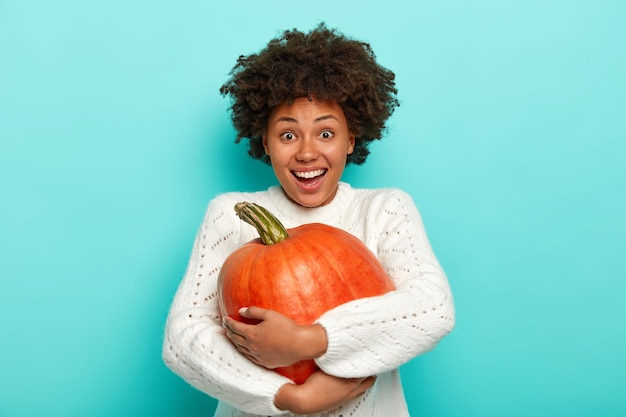 Isolated shot of happy afro woman enjoys autumn season, holds big ripe pumpkin, picks up vegetable from autumnal garden, has joyful expression, wears white sweater, models against blue background