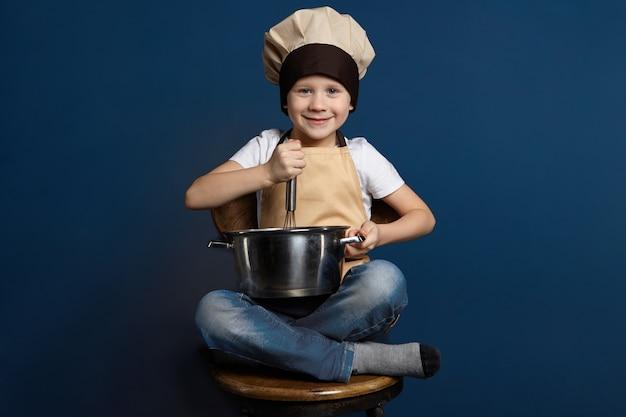 Colpo isolato di bambino maschio allegro felice in jeans, copricapo da chef e grembiule, seduto a gambe incrociate sulla sedia di legno, tenendo la casseruola, sbattendo le uova con lo zucchero mentre si prepara la pasta per la torta