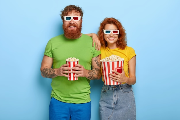 Isolated shot of happy ginger woman and her bearded husband come in cinema on eveing performance, have glad faces and smiles, wear three dimension glasses, eat delicious snack while watching movie