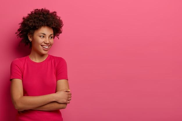 Colpo isolato di felice ragazza millenaria guarda volentieri lontano, vestito con abbigliamento casual, nota qualcosa di divertente giusto, sta contro il muro rosa, uno spazio vuoto per il tuo contenuto pubblicitario o testo