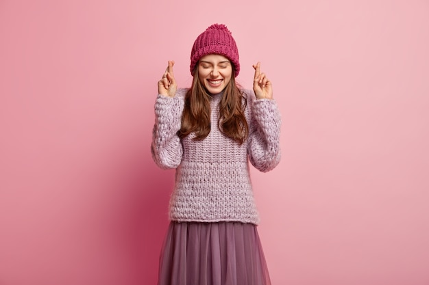 Isolated shot of happy pleased european woman believes in luck, closes eyes in pleasure, smiles broadly, wears knitted jumper, skirt and headgear, poses over rosy wall, still hopes for good fortune