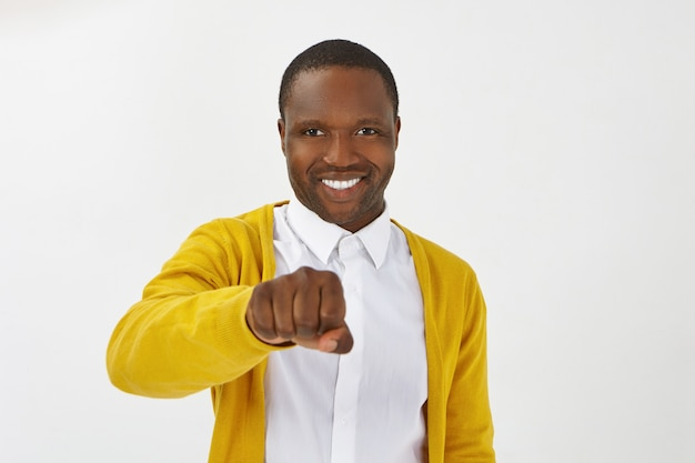 Isolated shot of happy positive young afro american man wearing stylish clothes posing , smiling broadly and holding clenched fist in front of him, ready to bump knuckles while greeting you