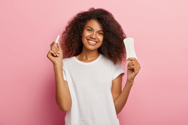 Isolated shot of happy young afro female holds menstuation cotton tampon and sanitary napkin