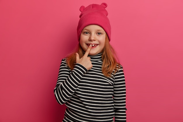 Isolated shot of little child rejoices having new adult tooth, has ginger hair, dresed in striped sweater and stylish hat, has charming positive expression poses over rosy wall. look at my white teeth