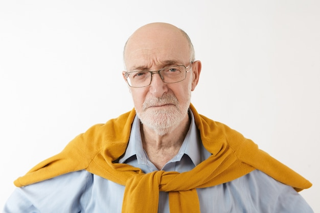 Isolated shot of mature male history teacher with gray stubble having serious stick facial expression standing with copyspace for your text or information
