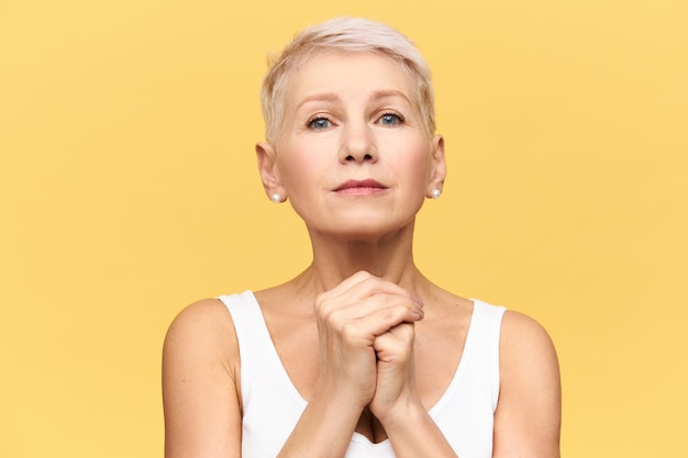 Isolated shot of modern blonde european mature woman in tank top keeping hands under her chin staring  with nervous upset look, eyes full of hope, begging, pleading, worrying about something