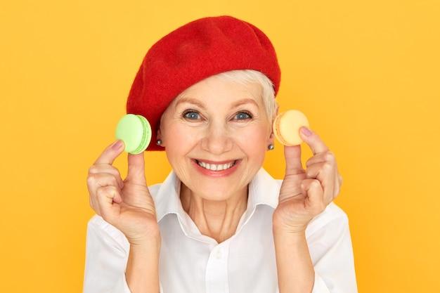 カラフルなフランスのクッキーを保持しているカメラで広く笑っている赤いボンネットの愛らしい面白いシニア女性年金受給者の孤立したショット。