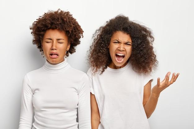 화가 난 불쾌한 두 민족 자매의 고립 된 샷이 실패하고 화가 나서 비명을 지 릅니다.