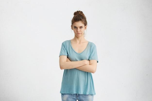 Изолированный снимок разгневанной жены, скрещенной за руки, скептически и недовольно глядя