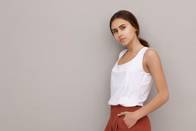 Изолированный снимок привлекательной милой молодой кавказской женской модели, одетой в стильную одежду, стоящую у пустой стены с copyspace для вашего текста или рекламной информации