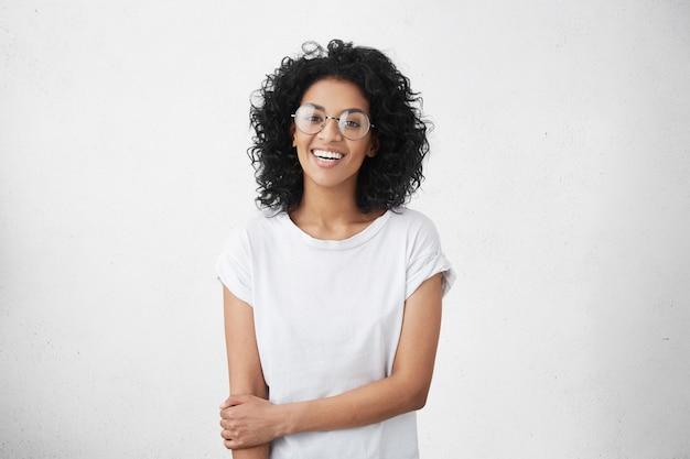 丸いアイウェアの魅力的な浅黒い肌の学生の女の子の分離ショット