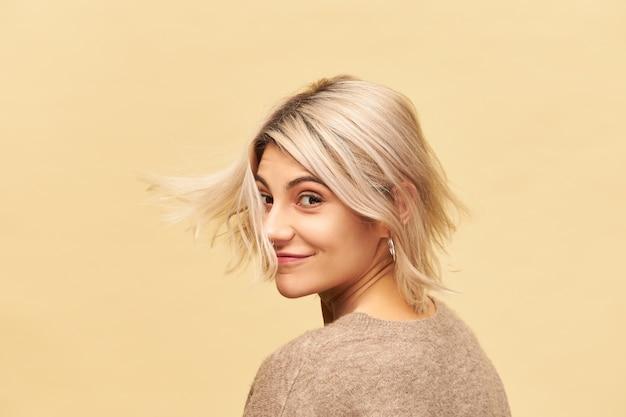 Изолированный снимок привлекательной модной молодой женщины с прической боб и пирсингом на лице, танцующей у глухой стены, счастливо улыбаясь, наслаждаясь приятным временем, весело, ее светлые волосы развевались на ветру