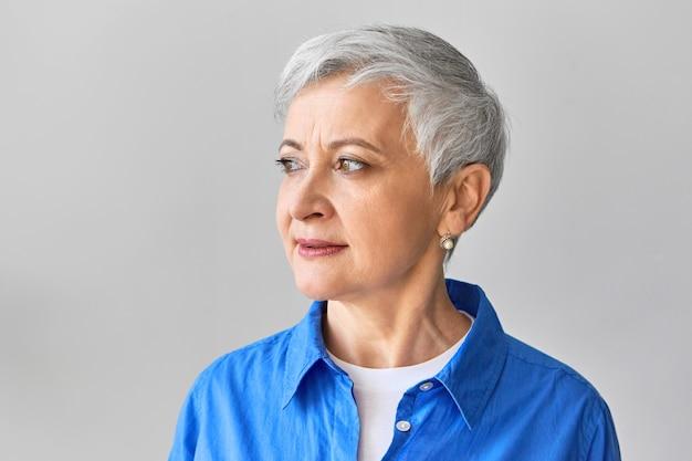 真珠のイヤリングと青いシャツを着て、物思いにふける真剣な表情で目をそらしている白い上に魅力的な60歳の白髪の女性の孤立したショット。人とライフスタイルのコンセプト