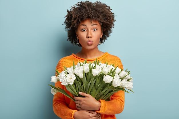 巻き毛の美しい黒人の若い女性の孤立したショットは、白いチューリップの素敵な花束を保持し、唇を折りたたんで、オレンジ色のジャンパーを着て、青い壁に隔離されています。春の時間の概念