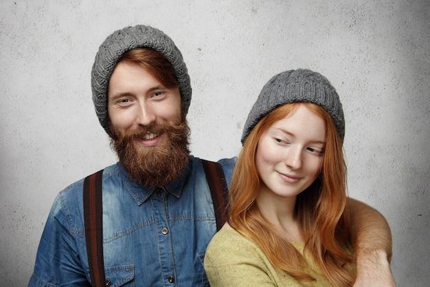 Изолированные выстрел красивая счастливая пара в теплых серых вязаных шапках