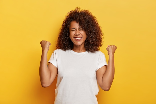 Изолированный снимок красивой успешной женщины с вьющимися волосами, поднимающей сжатые кулаки, празднует триумф, будучи очень довольным и счастливым, закрывает глаза от удовольствия, носит белую футболку. да, у меня получилось!