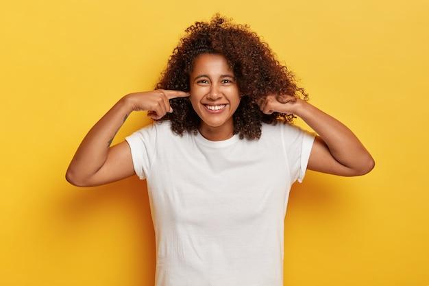 穏やかな幸せな女性の孤立したショットは、耳を塞ぎ、パーティーで楽しんで、大音量の音楽を無視し、リラックスして満足し、ノイズを聞いていない、面白い表情をしている、白い服を着ている、黄色い壁の上のモデル