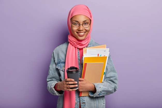 쾌활한 이슬람 여자의 고립 된 샷은 테이크 아웃 커피를 보유하고, 서류와 함께 메모장을 운반하고, 휴식과 뜨거운 음료 시간을 가지고, 전통적인 분홍색 히잡을 착용하고, 바이올렛에 고립 된 좋은 감정을 표현합니다.