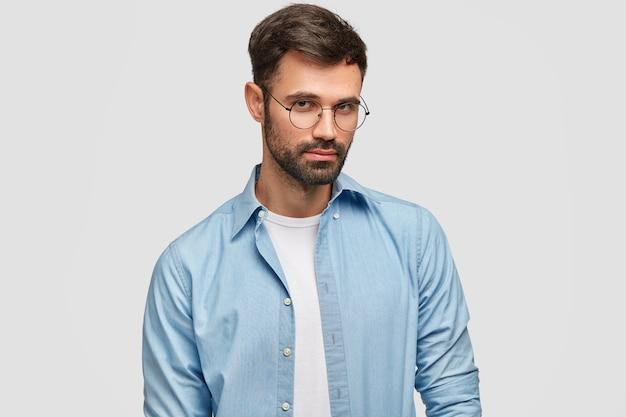 자신감이 심각한 형태가 이루어지지 않은 백인 남성의 고립 된 총 흰색 벽 위에 절연 파란색 유행 셔츠를 입고 라운드 안경을 통해 보인다. 사람, 생각, 라이프 스타일 개념