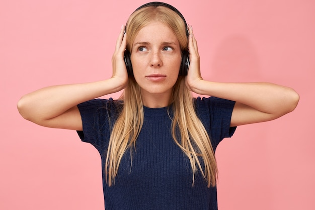 Изолированный снимок симпатичной девочки-подростка, держащей руки за уши, наслаждаясь высококачественными музыкальными треками в mp3-плеере с помощью беспроводной гарнитуры