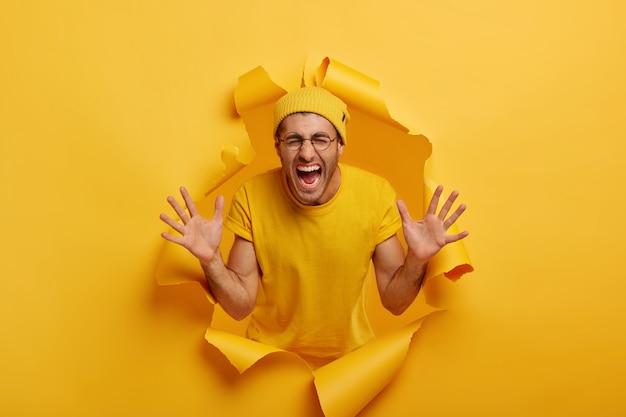 Изолированный снимок эмоционального молодого человека, поднимающего обе ладони к камере, громко кричащего, открывающего рот, одетого в повседневную одежду